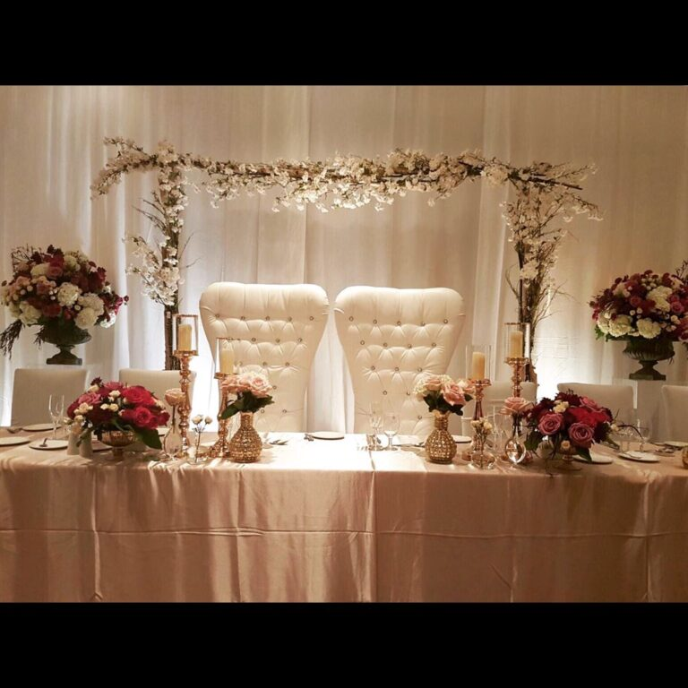 pair of white upholstered chair in head table setting